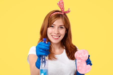 Lovely young housemaid in headband, rubber protective gloves, uses washing spray and sponge for cleaning mirror, smiles positively, isolated over yellow background, rejoices finishing housework