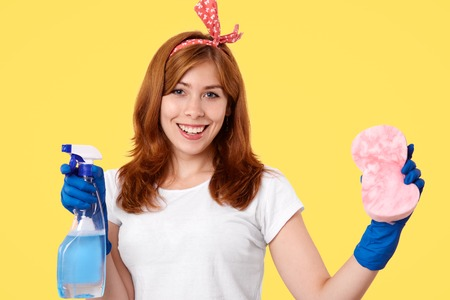 Cheerful young female housemaid wears casual t shirt and headband, holds washing spray and sponge, going to clean dust, being in blue rubber protective gloves, isolated over yellow background