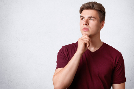 Horizontal shot of thoughtful male with appealing appearance and strong healthy body, holds chin, concentrated on something, contemplates about future family life, poses against white background Banco de Imagens