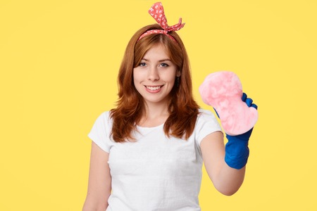 Positive young female does overalls cleaning up in her apartment, enjoys process, wears rubber blue gloves, holds sponge, isolated over yellow background. Housewife with mop. Cleaning concept Banque d'images