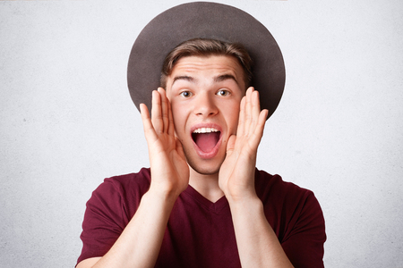 Portrait of happy Caucasian male exclaims joyfully, keeps mouth opened, wears elegant hat and t shirt, being in high spirit, isolated over white background. People, positiveness and lifestyle concept
