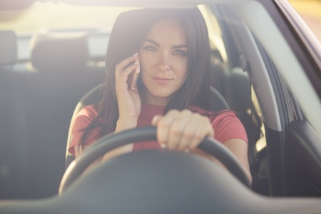 Beautiful brunette young female driver speaks via modern cell phone while driving car, has serious exression, discusses something with friend, being stuck in traffic jam, looks through windshiled Stock Photo - 108850182