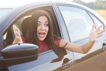 Astonished beautiful female exclaims with shock, gestures with hands, looks through car window, notices something terrible on road, has amazed facial expression. Woman driver reacts on accident