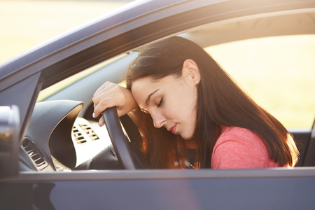 Transportation concept. Tired beautiful woman driver has sleepy expression, stop on road as can`t drive any more, wants to have rest, leans at wheel, poses in car, feels overworked and fatigue Stok Fotoğraf