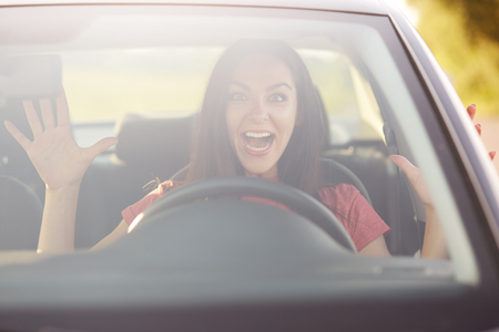 Emotions, driving and speed concept. Surprised female driver gestures with both hands, likes risk, takes off hands from wheel while drives car, has glad and shocked expression, enjoys speed on road