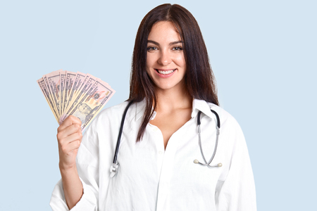 Medicine and corruption concept. Happy young professional female doctor holds money in hands, happy to recieve bribe from patients, wears white robe and phonendscope, isolated over blue background Stock Photo