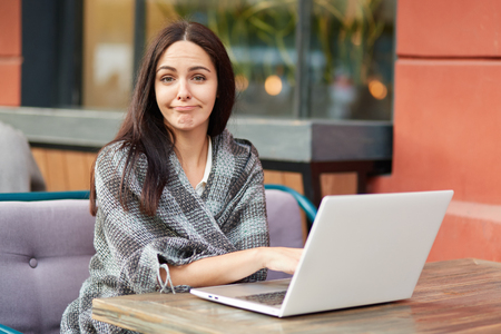 Puzzled tired female freelancer makes online research of information, wrapped in warm coverlet, poses against cafe interior. Attractive woman student studies online courses or going to watch webinar