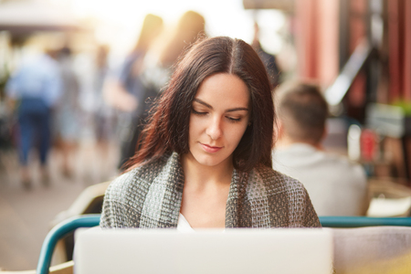 Horizontal shot of gorgeous female with attractive appearance, has serious concentrated look into laptop computer, works on innovative project, develops new strategy, sits in outdoor coffee shop