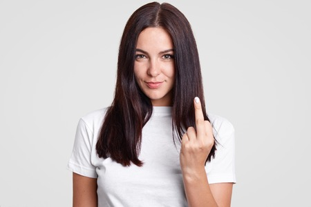 Bad girl with straight dark hair shows fuck sign, looks mysteriously at camera, wears casual t shirt, isolated over white background. Young brunette young woman shows middle finger. Fuck off!