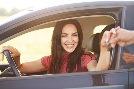 Happy Cuacasian young female takes car key from her husband, recieves expensive gift, going to drive automobile, has broad smile, being in high spirit. People, transport and driving concept.