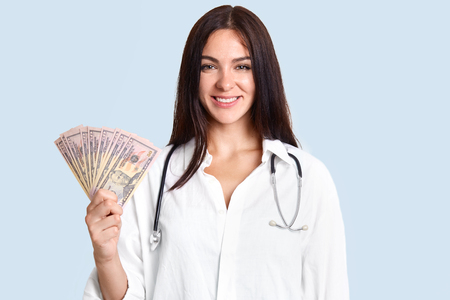 Cheerful happy brunette female doctor in white robe, holds cash, earns salary by curing patients, stands against blue background. Young woman involved in corruption, takes money from people.