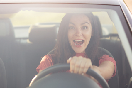 Emotional young female driver exclaims from surprisement, notices something strange on road, has shocked facial expression, opens widely eyes and mouth, stare through windshiled. Danger on road
