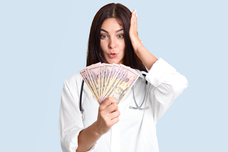 Stunned female physician with dark hair, looks surprisingly at dollars, recieves huge bribary, involved in corruption, isolated over blue background. Medicine, finance and compensation concept