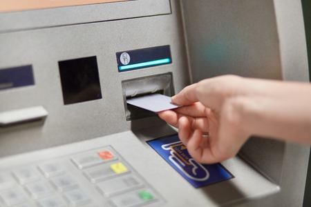 Someone takes off money from outdoor bank terminal, inserts plastic credit card in atm machine, going to withdraw money and get salary. Cash machine. Modern technologies and innovations concept