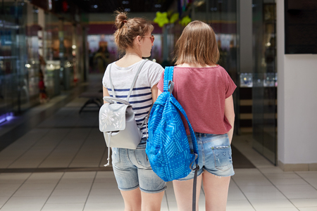 Back view of two young females with rucksack stroll in shopping mall, makes purchases, wears denim shorts and casual t shirt, try to find clothes with discounts, have rest during weekend or day off Stok Fotoğraf