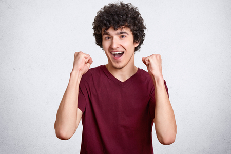 Male winner with curly hair, clenches fists and exclaims with happiness, dressed in casual outfit, celebrates his victory or triumph, models in studio against white background. Success concept