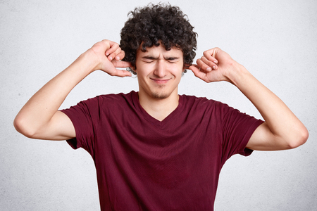 Horizontal shot of displeased man has curly hair, plugs ears, keeps eyes closed, doesnt want to hear loud noise, ignores somebody, wears loose t shirt, isolated over white background. Dont bother me Standard-Bild