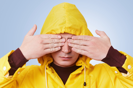 Serious young male wears yellow anorak and hood, covers eyes with hands, anticipates for surprise or tries to hide himself. Fashionable hipster guy gestures against light blue studio background Banco de Imagens