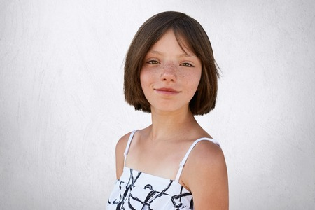 Portrait of freckled little girl with dark short hair, hazel eyes and thin lips wearing black and white dress, posing at camera against white background. Adorable girl with freckles. Childhood concept
