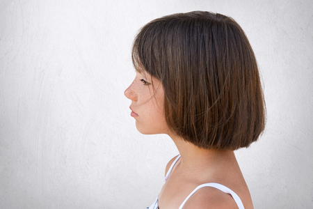 Sideways portrait of adorable freckled girl looking into distance while having dreamy expression isolated over white concrete wall. Little girl with short dark hair standing sideways with serious look
