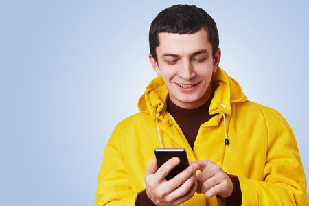 Portrait of cheerful attractive young man uses modern cell phone, surf social networks, glad read pleasant comments on his photo, isolated over blue wall. Successful blogger develops his website