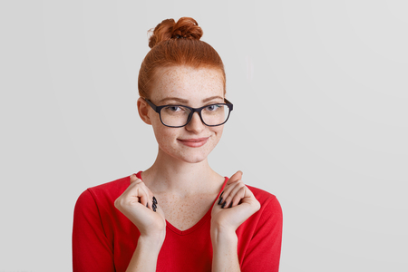 Delightful red haired beautiful young female with freckled skin wears glasses, keeps hands pressed, dressed in red sweater, anticipates for something intriguing, isolated over white background.
