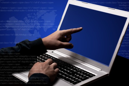 Unrecognizable hacker steals data information, works on laptop computer, points at screen, involved in computer crime, poses against dark blue background. Double exposure. Internet crime concept Stock Photo