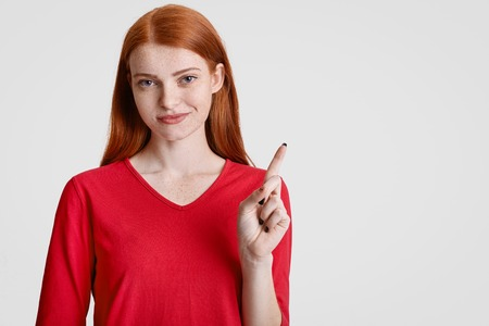 Satisfied redhaired freckled young female in red clothes, points with fore finger at upper right corner, indicates at blank space for your advertisement or promotional text. Look aside, please! Foto de archivo
