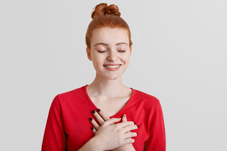 Positive redhead smiling female closes eyes and has cheerful expression, keeps hands on chest or heart, expresses positiveness and her sympathy, isolated over white background. My heart is for you