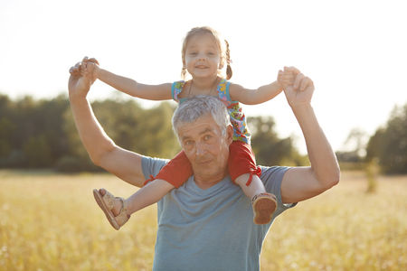 People, relationship concept. Horizontal shot of serious grey haired handsome grandfather gives piggyback to his small granddaughter, stand on green meadow, have fun together, being friendly family