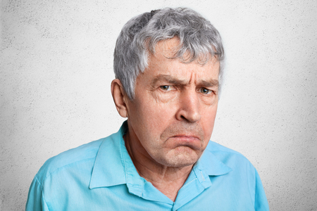Displesed unhappy wrinkled mature male frowns face and curves lips, wears formal shirt, poses against white concrete background. Close up of elederly man dissatisfied with ammount of pension