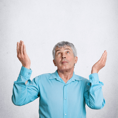 Vertical shot of attractive grey haired mature elderly male prays and asks God for something desirable, looks upwards with great hope, poses against white background with blank space above head Stock Photo