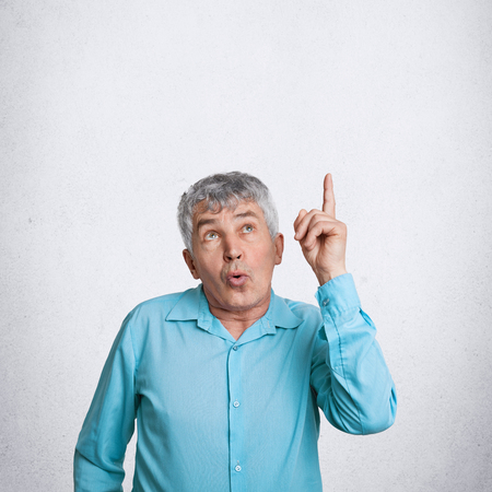 Indoor vertical shot of amazed elderly male indicates upwards as notices something surprising, dressed in elegant shirt, poses against white background with copy space for your advertisement