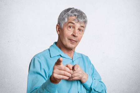 Mature male chooses you, indicates with fore fingers at camera