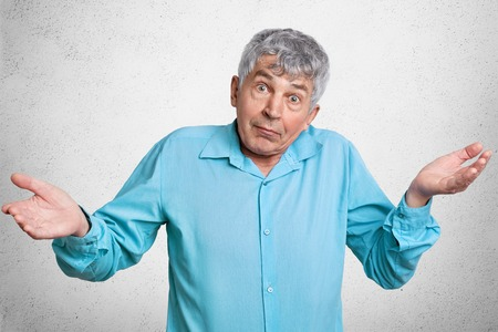 Elderly puzzled male with grey hair feels uncertain about something, shrugs shoulders, dressed in fromal clothing, stands against white concrete wall. Mature attractive man looks in bewilderment Stock Photo