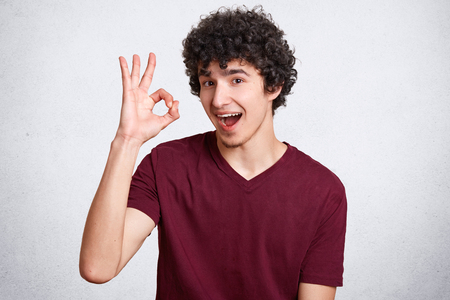 Everything will be fine! Satisfied curly man looks with assured and happy expression, shows ok sign, demonstrates his readiness and awareness, dressed in casual t shirt, isolated over white background