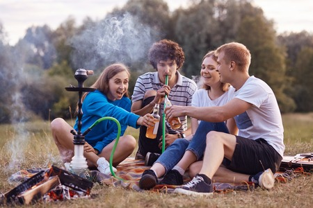 Teenagers have fun. Joyful girls and boys spend weekend outdoor on picnic, smoke hookah, clink bottles with energetic drinks, celebrate starting holidays. Friendship, youth and lifestyle concept Stock Photo