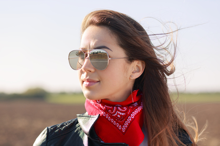 Rock style. Close up shot of dark haired thoughtful woman dressed in leather jacket, red bandana and sunglasses, focused into distance outdoor.