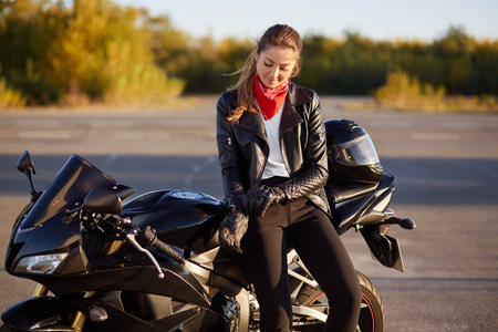 Outdoor shot of pleased female bikes puts on leather gloves, dressed in black clothes, poses on motorbike Archivio Fotografico