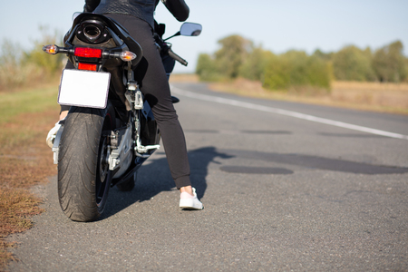 Cropped image of unrecognizable female bikes poses back on bike at asphalt, wears black clothes, blank copy space aside for your advertisement or promotional text.