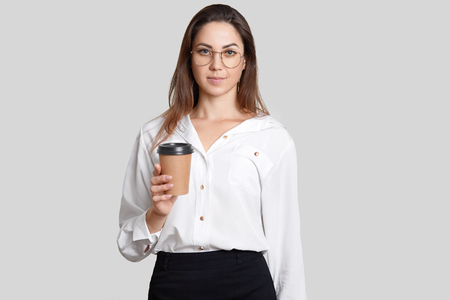 Young student in formal clothes, holds takeaway coffee, wears transparent glasses, holds disposable cup, isolated over white background, has break after classes. Businesswoman with espresso.
