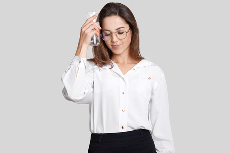 Tired sad woman keeps glass of water near head, feels thirsty and overworked, dressed in stylish formal clothes, isolated over white background. People, work, weariness and lifestyle concept