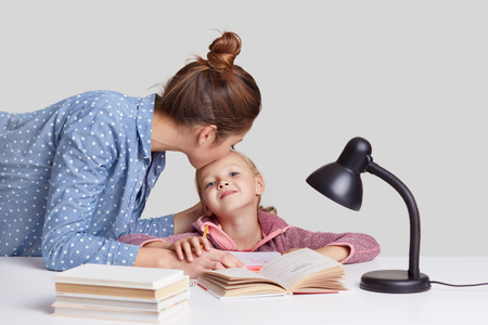 Photo of young woman cares of her child, kisses daughter in forehead, praises her to study well, explains material, read books and prepare for lessons at school, isolated on white. Archivio Fotografico