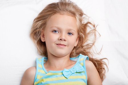Close up shot of blue eyed small child looks pleasantly at camera, wears casual nightwear, has good rest in bed, being in good mood after having healthy sleep. Childhood, sleeping and home concpet Stok Fotoğraf
