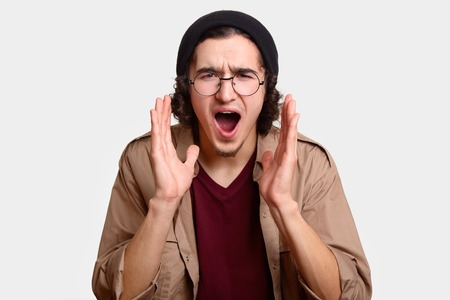 Headshot of angry desperate hipster guy opens mouth widely, keeps both hands near mouth, exclaims with irritation, wears round spectacles and black headgear, isolated over white studio background