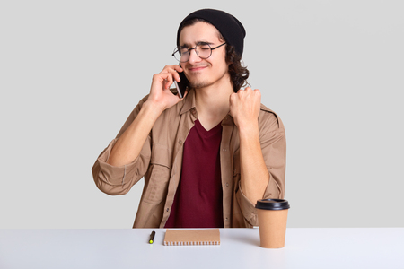 Pleased hipster enjoys conversation via cell phone with girlfriend, sits at desktop alone, uses notepad and pen for writing notes, drinks hot beverage, isolated over white background. Communication Archivio Fotografico