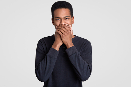 Photo of handsome man covers mouth with both hands, has surprised expression, being mute, has eyes full of disbelief, dressed in casual black sweater, isolated over white background. Omg concept