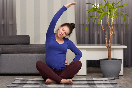 Photo of beautiful woman expects child, does sport at home, practices sport exercises, poses in modern apartment, wears blue sweater and leggings, raises hands, has healthy lifestyle during pregnancy