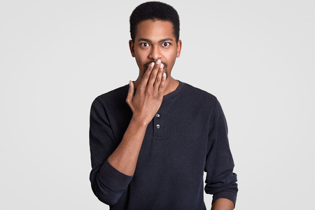 Indoor shot of stupefied handsome Afro American man covers mouth with surprisement, exclaims in surprisement, has eyes popped out, wear casual clothes, isolated over white background. Omg concept