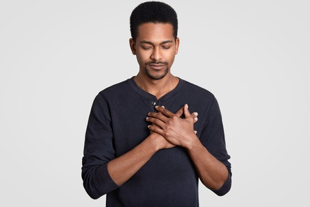 Photo of black man with faithful expression, keeps hands on chest, expresses sympathy, closes eyes, feels gratitude, dressed in sweater, models against white background. Body language concept